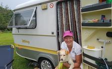 Nicolette Verkleij voor haar kleine caravan. 'Een echte Eriba, mét hefdak. Ik heb hier precies alles wat ik nodig heb. Een goed bed, een wc'tje, een koelkast, een elektrische kookplaatje. De Eriba is mijn rugzak.'