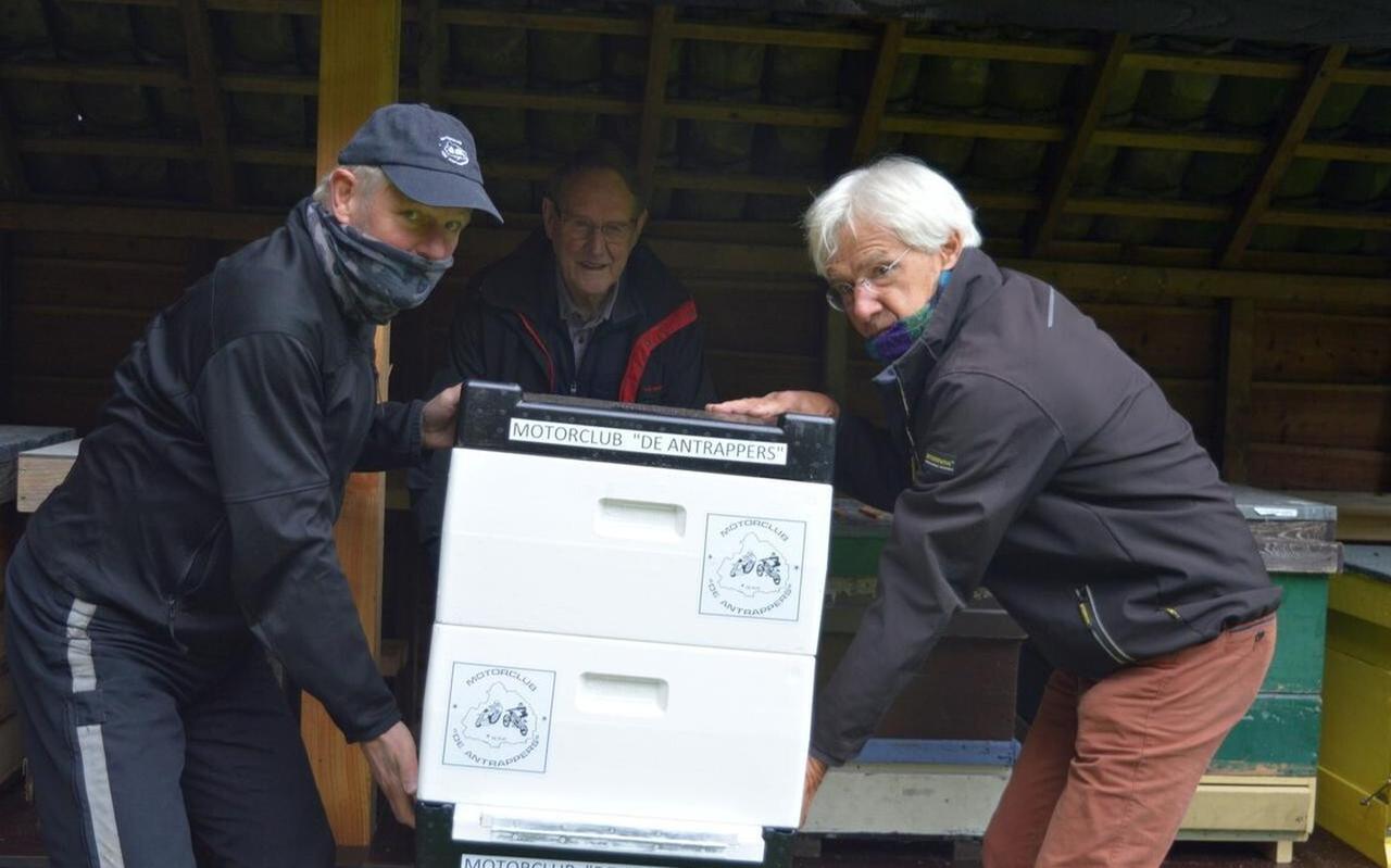 Arend Klomp (links) en Theo Hulshof plaatsen de bijenkast die nu van de Antrappers is. Op de achtergrond kijkt Jan huizing mee, hij is penningmeester van de Antrapper s én imker.