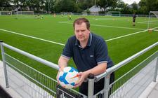 Trainer John Kramer poseert bij het kunstgrasveld van SV Pesse.