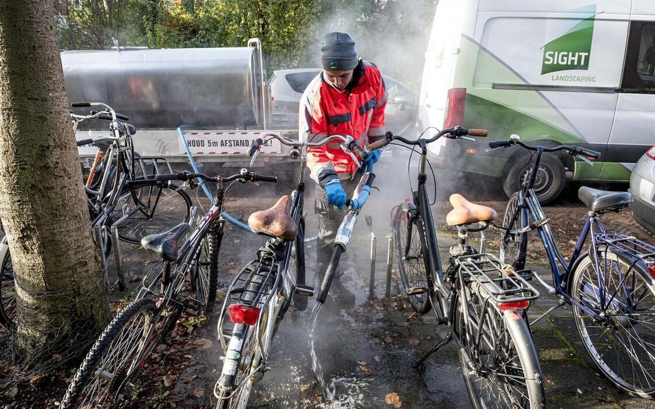 Jim Hamstra van Sight Landscaping haalt tussen geparkeerde fietsen onkruid weg met kokend water. Machines werken op zulke plekken niet.