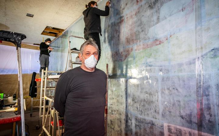 Restaurateur Fabian Rasson voor de muurschildering, die nu in Zeeland ligt om gerestaureerd te worden.