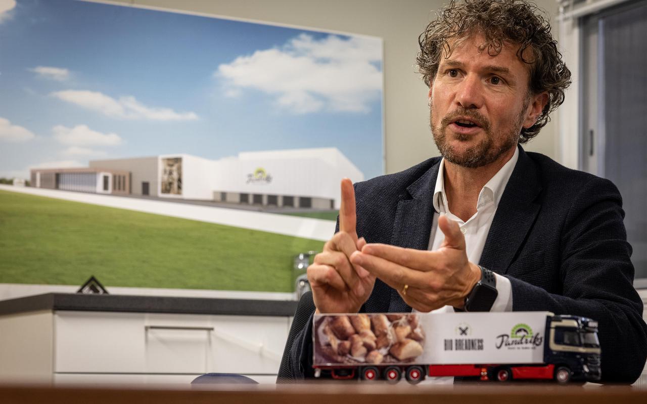 Peter van den Berg met op de achtergrond een weergave van het nieuwe gebouw.