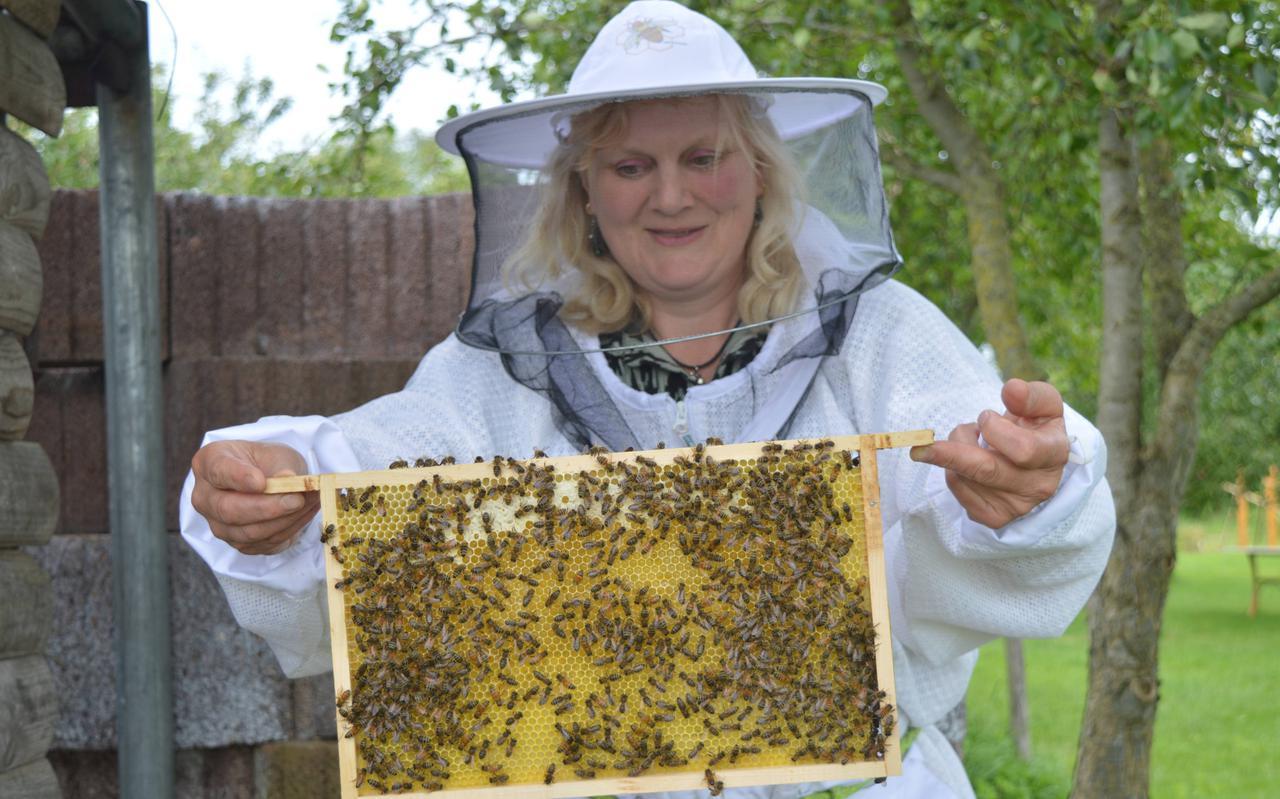 Imkerin Angelique Schipper toont een raat vol bijen uit één van de bijenkasten.