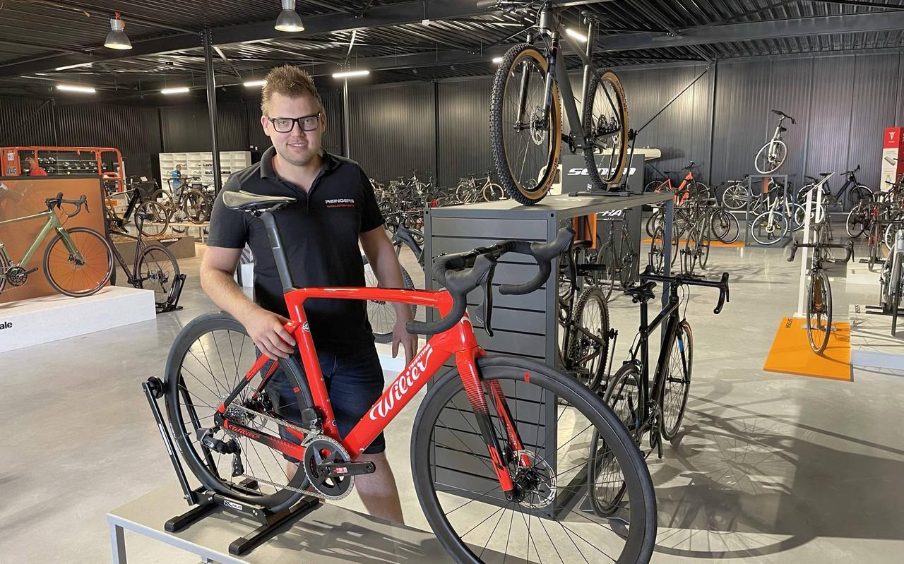 Eigenaar Henk Reinders met een fraaie rode Wilier racefiets in de nieuwe winkel.